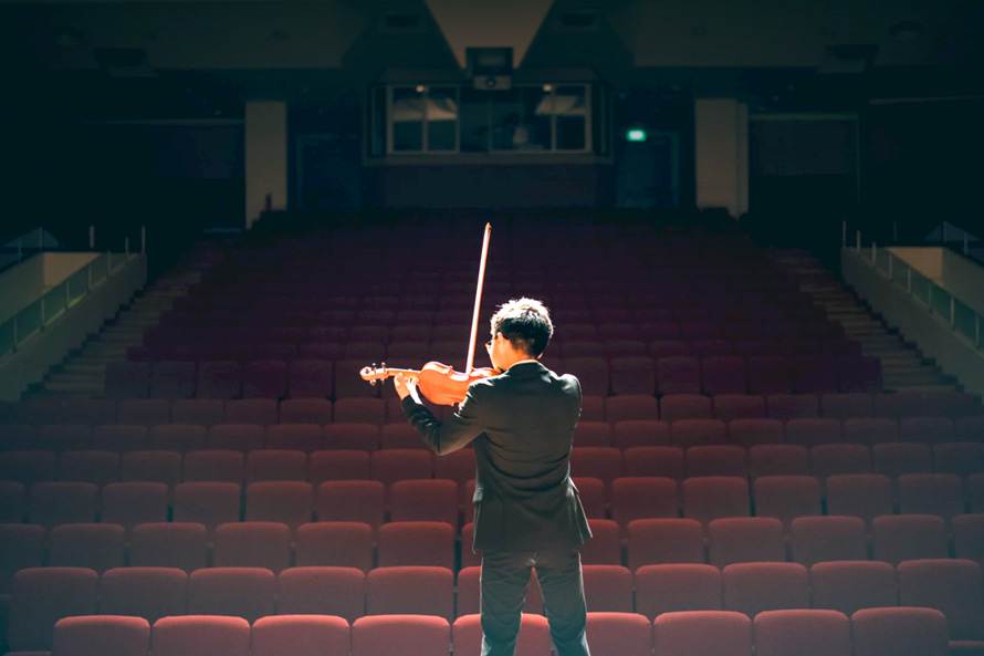 man-rehearses-for-event-on-stage-violin